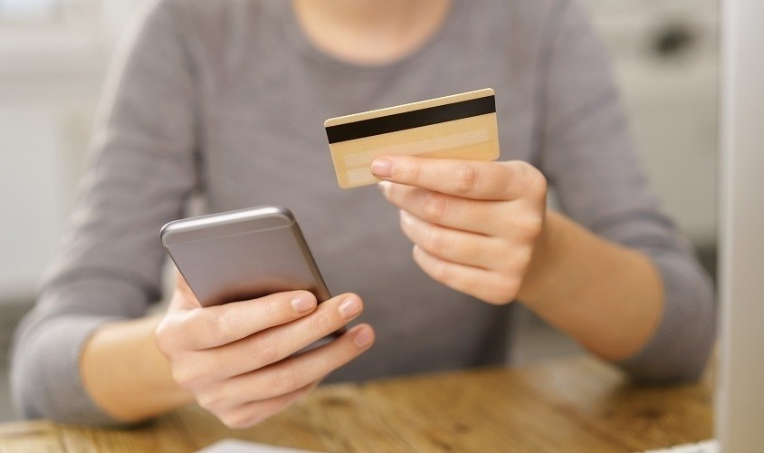 Woman with mobile phone and credit card